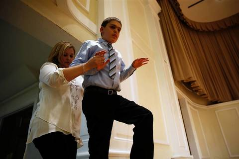 Joseph Williams gets help up the stairs from his Beethoven's Buddies instructor Beth Bauer before the 12-year-old played the piano at the Community School of Arts Choirs and Instrumental Concert at Wheaton College.