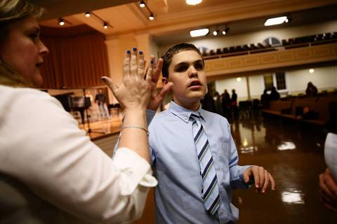 Joseph Williams gets a high-five from his instructor Beth Bauer after performing at Wheaton College.
