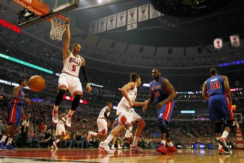 Carlos Boozer hangs on the rim after getting the dunk against the Pistons' Jason Maxiell in the first quarter.