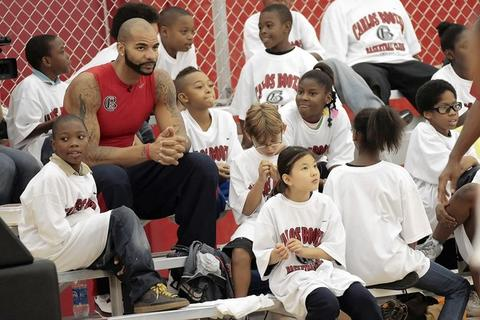 Carlos Boozer watches a game with children at his basketball clinic at The Chicago Bulls/White Sox Training Academy in Lisle.