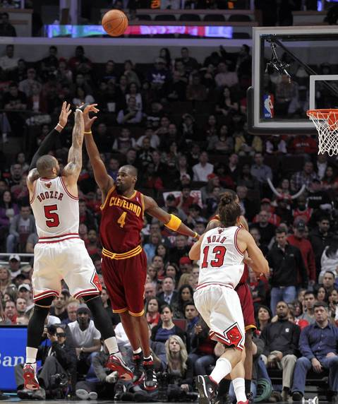 Carlos Boozer shoots a high-arcing shot over the Cavaliers' Antawn Jamison in the second quarter. The Bulls rolled, winning 107-75.