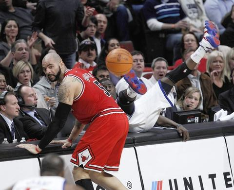 Carlos Boozer and Philadelphia's Jrue Holiday end up on the scorer's table during the second half.