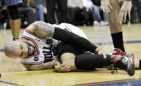 Carlos Boozer grabs his ankle after being intentionally fouled during the second half against the Bobcats.