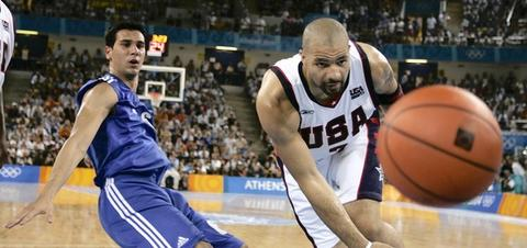 USA's Carlos Boozer and Greece's Nikolaos Zisis watch a loose ball go out of bounds during a 77-71 win in a preliminary round game in Athens, Greece.