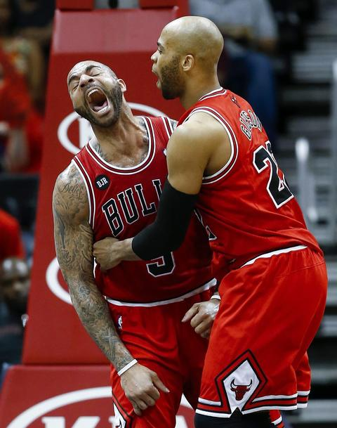 Carlos Boozer and Taj Gibson (R) celebrate Boozer's dunk against the Hawks during the second half.