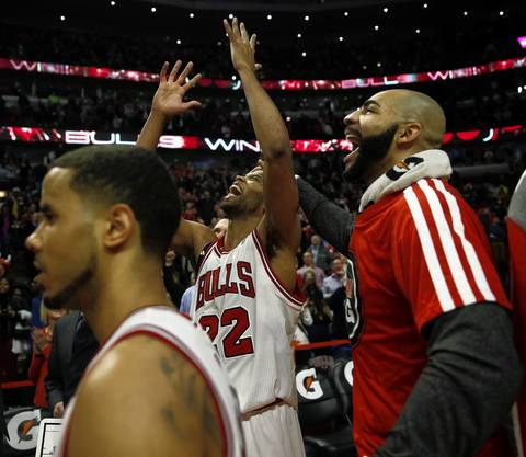 Taj Gibson and Carlos Boozer celebrate Gibson's game-winning basket during a 102-100 overtime win over the Lakers at the United Center.