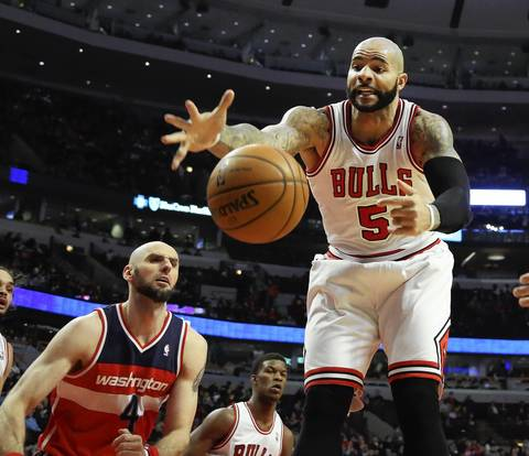 Carlos Boozer tries to stop a ball from going out of bounds in front of the Wizards' Marcin Gortat.