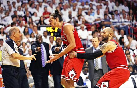 Carlos Boozer restrains Joakim Noah as he was going after a referee during the first half of Game 5 against the Heat.