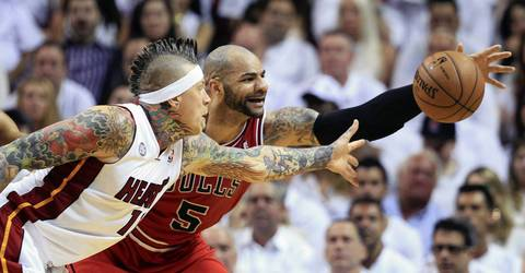 Carlos Boozer and the Heat' Chris Andersen reach for loose ball during a playoff game.