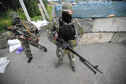 Pro-Russian armed men, wearing black and orange ribbons of St. George, a symbol widely associated with pro-Russian protests in Ukraine, stand guard at a checkpoint in Slaviansk, eastern Ukraine.