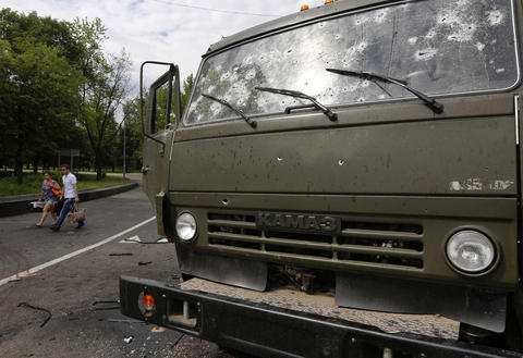 A couple walks past a wrecked Kamaz truck as they flee an area near the Donetsk airport on May 27.