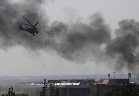 A Ukrainian helicopter Mi-24 gunship fires its cannons against rebels at the main terminal building of Donetsk international airport on May 26.