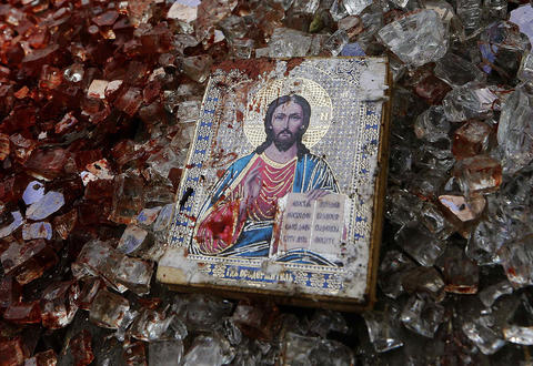 A bloodstained icon of Jesus is seen among blood-soaked shattered glass atop a wrecked Kamaz truck near the Donetsk airport on May 27.