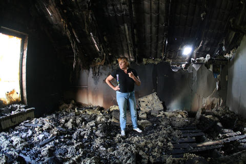 A woman looks at her building destroyed as a result of Monday's combat of Ukrainian troops with pro-Russia separatists near the International airport in Donetsk on May 27.