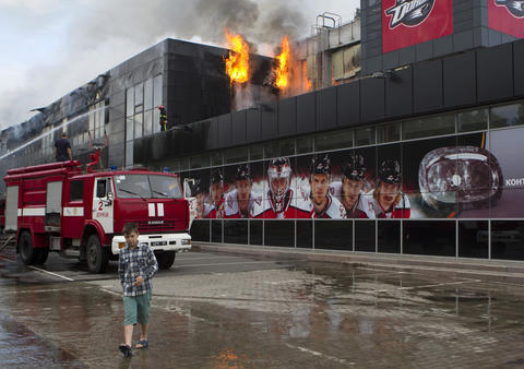 "A boy walks by as firefighters attempt to extinguish a fire at the sports arena ""Druzhba"" (Friendship), which is the home venue of the ice hockey club ""Donbass"" in Donetsk on May 27."