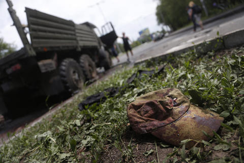"A blood-stained military cap is left on the ground near a wrecked truck of supporters of the self-proclaimed ""Donetsk People's Republic"" on a road leading to the Donetsk International Airport , in Donetsk, Ukraine, on May 27."