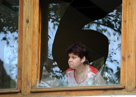 A woman looks out from a broken window in a bakery after a night of combat between pro-Russia separatists with Ukrainian troops in the eastern Ukrainian city of Slavyansk on May 27.