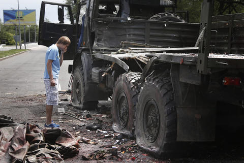 "A local man looks at damage near a wrecked truck of supporters of the self-proclaimed ""Donetsk People's Republic'"" on a road leading to the Donetsk International Airport, in Donetsk, Ukraine, on May 27."