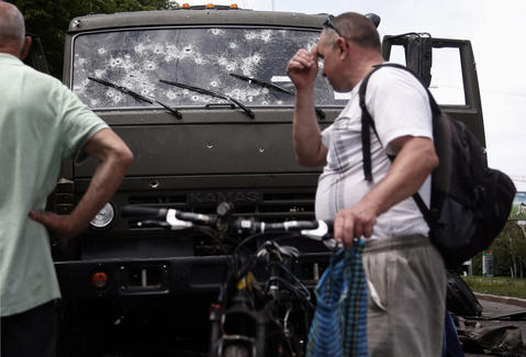 "Local men look at the bullet-ridden windshield of a wrecked truck of supporters of the self-proclaimed ""Donetsk People's Republic"" on a road leading to the Donetsk International Airport, in Donetsk, Ukraine, on May 27."