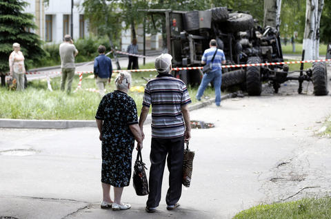 """Local residents look at a wrecked truck of supporters of the self-proclaimed """"Donetsk People's Republic"""" on a road leading to the Donetsk International Airport, in Donetsk, Ukraine, on May 27."""