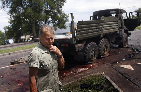 "A local woman is overcome with emotion as she looks at blood stains and damage around a wrecked truck of supporters of the self-proclaimed ""Donetsk People's Republic"" on a road leading to the Donetsk International Airport, in Donetsk, Ukraine, on May 27."