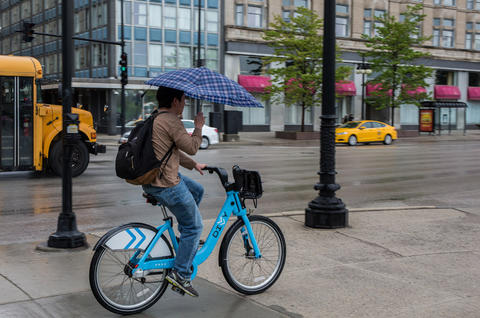 A person rides a Divvy bike at Michigan Avenue and East Congress Plaza Drive during rainy morning in Chicago on May 15, 2014.