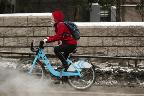 A woman rides a Divvy bike Feb. 14 down West Kinzie Street in Chicago.