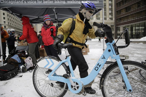 Susannah Chereskin of Chicago climbs on her Divvy bike outfitted in full ski mask and several layers of gloves after stopping at Daley Plaza on her morning commute on Jan. 21, 2014 to celebrate Winter Bike to Work Day with free Dark Matter coffee and Eli's Cheesecake organized by the Active Transportation Alliance.