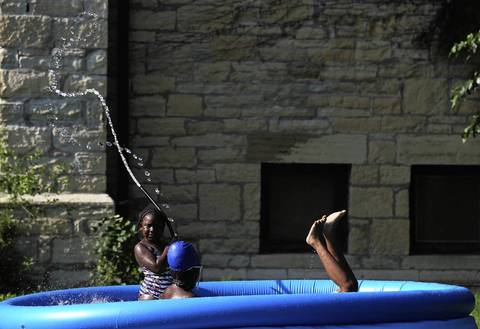 Journee Ashby, 5, left, Jasmine Sawyer, 10, center, and Nashan Fisher, 9, right, play in a pool outside Olivet Baptist Church, in Chicago.