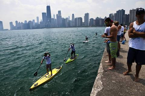 Bystanders watch as paddle board racers are compete in long distance courseof the 2012 Chicago World Paddle Challenge.