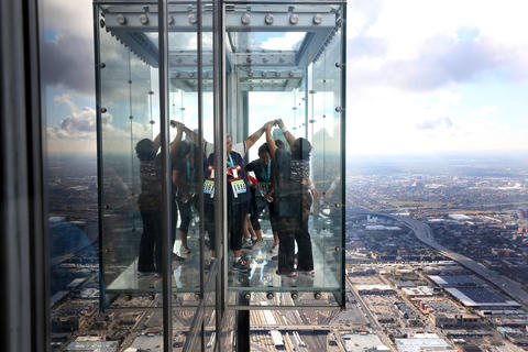 Race finishers take photos of themselves and one another in The Ledge after reaching the 103rd floor of the Willis Tower.