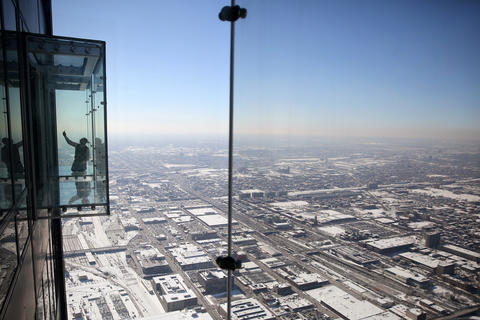 A man takes a self-photo on The Ledge at the Willis Tower Skydeck in Chicago.