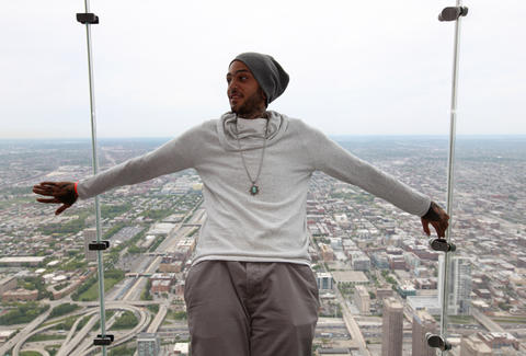 Travis McCoy, singer with Gym Class Heroes, stands on The Ledge of the Willis Tower.