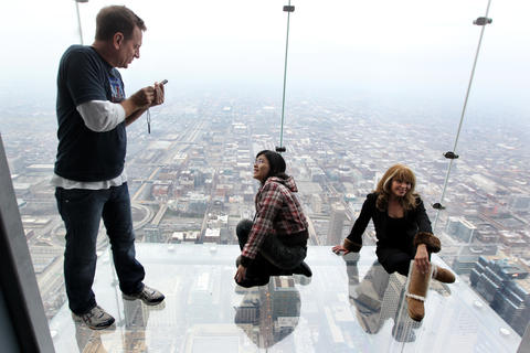 Maggie Lai, of Hong Kong, has her photo taken on The Ledge of the Skydeck at Willis Tower in Chicago.