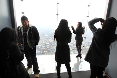 Tourists take turns posing for photographs on The Ledge of the Skydeck at Willis Tower.