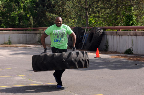 Michael Peterson, dean of students at New Britain High School, carries a truck tire during the annual Tough Man competition. He won the contest.