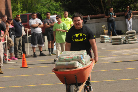 Carlo Vazquez, 15, a sophomore at New Britain High School pushes a wheelbarrow full of cement.