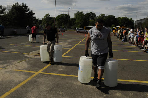 Jay Reyes, 17, a senior at New Britain High School, right, carries approximately 100 pounds of water in each hand.