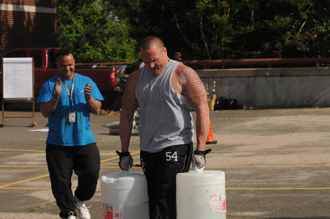 Jeff Marino, dean of 10th grade students at New Britain High School as a behavioral support assistant carries approximately 100 pounds of water in each hand.