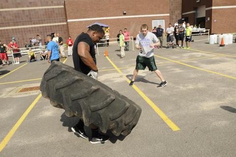 Lorenzo Baker, who works at New Britain High School as a behavioral support assistant carries a truck tire during the annual Tough Man competition.