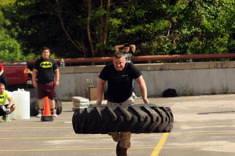 Sgt. Daniel Bump, of Athens, Pa., carries a truck tire during the annual Tough Man competition.