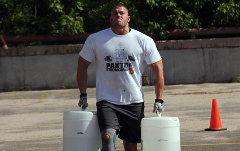Nate Slater, who works at New Britain High School as a behavioral support assistant carries approximately 100 pounds of water in each hand.