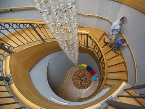 People walk down a staircase by a recently-installed kinetic chandelier at the Chrysler Museum of Art on Saturday, May 10. The museum is reopening after a $24 million expansion, including renovation of its galleries and complete reinstallation of its 40,000-object art collection.