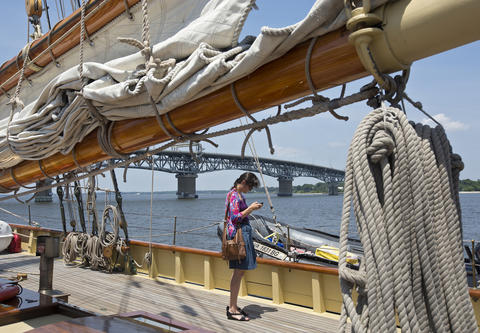 Stephanie Stabile checks her phone while touring the Schooner Virginia with her parents at the Yorktown waterfront on Thursday. The Virginia, an educational vessel which is homeported in Norfolk, docked for three days in Yorktown and offered free deck tours to the public.