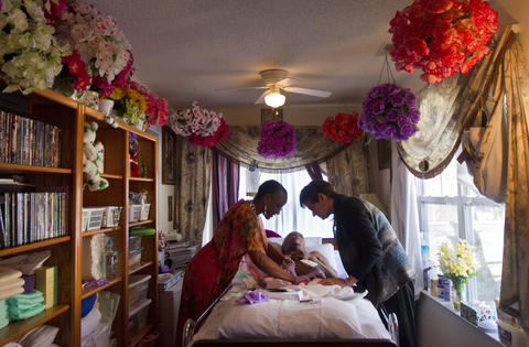 Etrulia Hurst and Dr. Teresa McConaughy tend to Willie Hurst, 78, a diabetic double-amputee who has suffered a stroke, during a home call on Wednesday in Yorktown. Dr. McConaughy, a Riverside physician, began seeing patients for Riverside's house calls program in February. She says the time to see patients in their own space allows her to provide more comprehensive care and foster more intimate relationships.