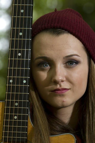 "Smithfield's Bria Kelly, 18, sits with her guitar in her backyard on May 7. Kelly returned home last week after she was eliminated by viewer vote on NBC's ""The Voice."""
