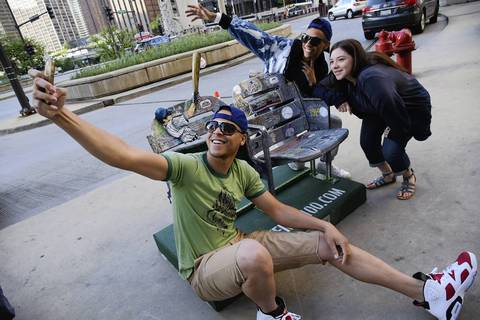 Anthony Steele, left, Oscar Chavez and Katarina Otero take a selfie by their Wrigley Field Centennial Seats representing the moment of the 1st game, in the 400 block of north Michigan Ave.