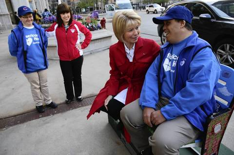 Misericordia resident Kris Huening, left, and Assistant Diredtor Julie O'Sullivan, second left, watch as Lois Gates and Paul Patterson of Misericordia Homes try out the Wrigley Field Centennial Seats in the 400 block of North Michigan Avenue after they were installed and unveiled.