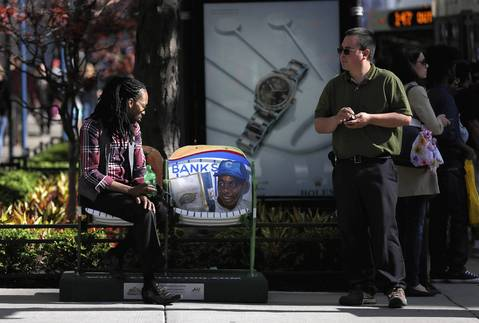 John Crawford of New York sits next to a painted Ernie Banks in a set of stadium seats on Michigan Avenue to commemorate the 100th anniversary of Wrigley Field.