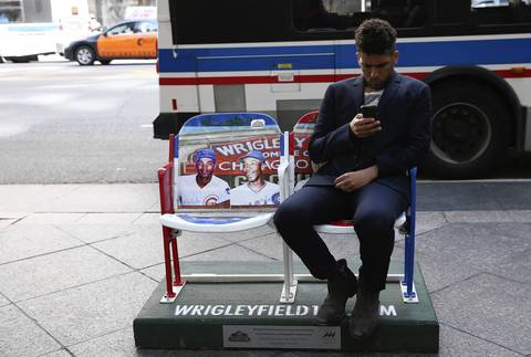 Brent Engelen sits in one of the 50 pairs of painted baseball stadium seats on Michigan Avenue in front of Banana Republic to commemorate the 100th anniversary of Wrigley Field.
